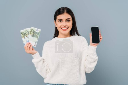 smiling pretty girl in white sweater holding euro banknotes and smartphone with blank screen isolated on grey