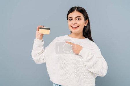 Photo pour Sourire jolie fille en pull blanc pointant avec doigt carte de crédit isolé sur gris - image libre de droit
