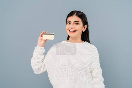 Photo pour Sourire jolie fille en pull blanc tenant carte de crédit isolé sur gris - image libre de droit