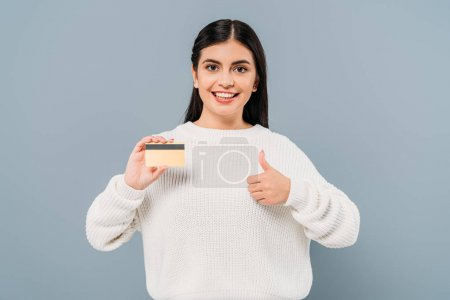 smiling pretty girl in white sweater holding credit card and showing thumb up isolated on grey