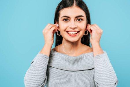 Photo pour Sourire enceinte jolie fille en utilisant des écouteurs sans fil isolé sur bleu - image libre de droit