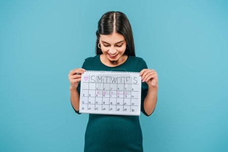 Photo pour Smiling pregnant girl looking at period calendar isolated on blue - image libre de droit