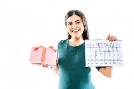 Photo pour Smiling pregnant girl holding present and period calendar isolated on white - image libre de droit