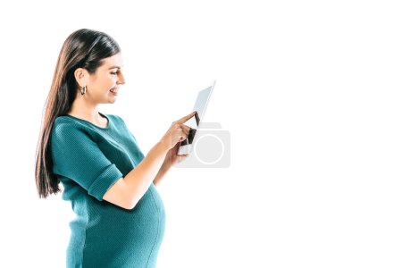 Photo for Side view of smiling pregnant girl using digital tablet isolated on white - Royalty Free Image
