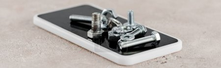 Photo for Metal screws and bolts on smartphone on grey background, panoramic shot - Royalty Free Image
