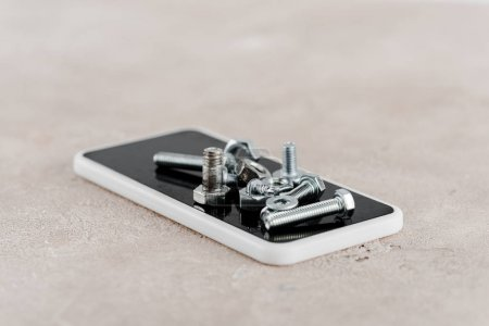 Photo for Metal screws and bolts on smartphone on grey background - Royalty Free Image