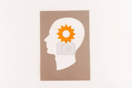 Photo pour Top view of human head silhouette with orange gear isolated on white - image libre de droit