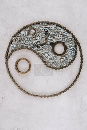 Photo pour Top view of aged metal gears and screws arranged in taijitu symbol on grey background - image libre de droit
