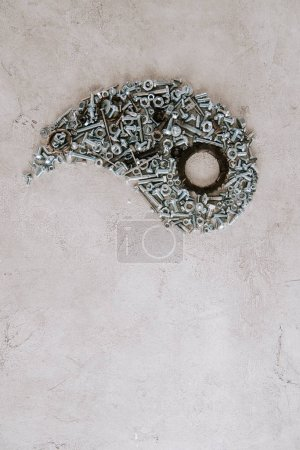 Photo pour Top view of aged metal screws arranged in part of taijitu symbol on grey background - image libre de droit