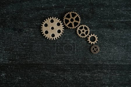 Photo for Top view of retro metal gears on dark wooden background with copy space - Royalty Free Image