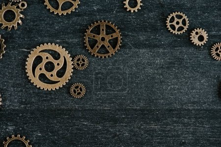 Photo for Top view of vintage metal gears on dark wooden background with copy space - Royalty Free Image