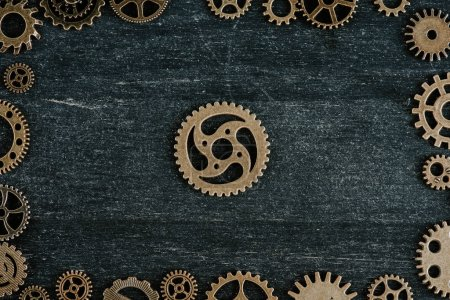 Photo for Top view of vintage metal gears arranged in frame on dark wooden background - Royalty Free Image