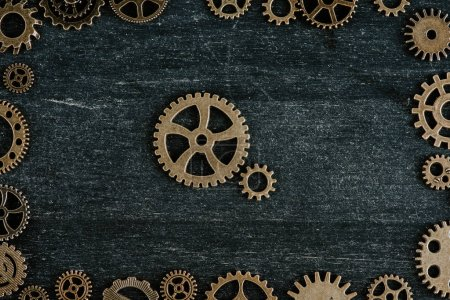 Photo for Top view of vintage metal gears in frame on dark wooden background - Royalty Free Image