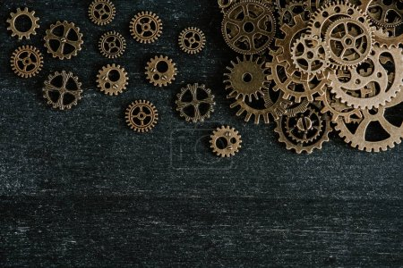 Photo for Top view of aged metal gears on dark wooden background - Royalty Free Image