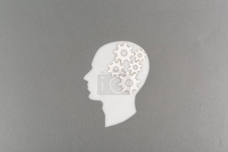 top view of cut out white human head with gears isolated on grey