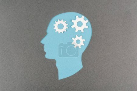 top view of cut out blue human head with white gears isolated on grey