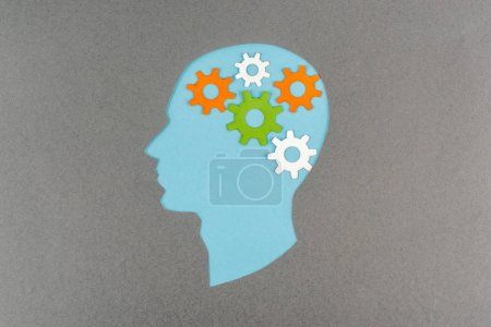 Photo pour Top view of cut out blue human head with colorful gears isolated on grey - image libre de droit