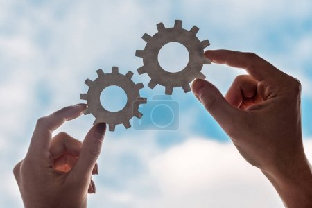 cropped view of man and woman holding gears on blue sky background