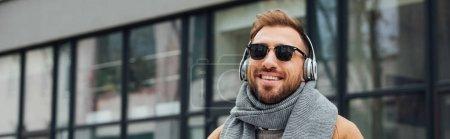 Photo pour Vue panoramique de l'homme souriant dans des lunettes de soleil et des écouteurs à l'extérieur - image libre de droit