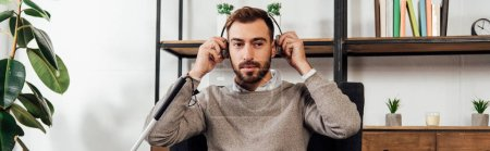 Photo for Panoramic shot of visually impaired man using headphones in living room - Royalty Free Image