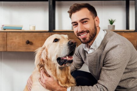 Photo for Smiling man looking at camera while petting golden retriever at home - Royalty Free Image