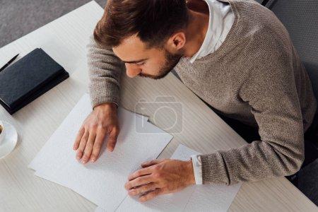 Photo pour Vue en angle élevé sur les malvoyants lisant la police braille à la table - image libre de droit