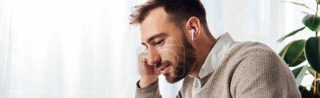 Photo pour Vue latérale de l'homme utilisant des écouteurs sans fil à la maison, vue panoramique - image libre de droit