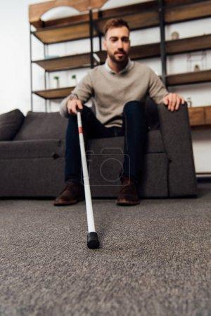 Photo pour Concentration sélective de l'homme malvoyant tenant un bâton de marche assis sur le canapé dans le salon - image libre de droit