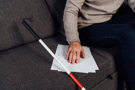 Photo pour Cropped view of blind man reading braille font beside walking stick on sofa - image libre de droit