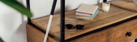 Panoramic shot of walking stick beside sunglasses and books on cupboard shelf