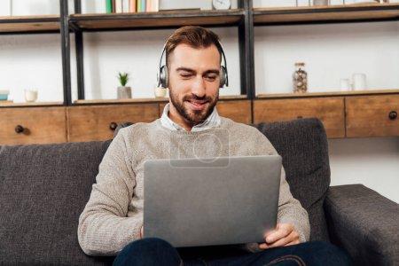 Photo pour Smiling man in headphones using laptop on sofa in living room - image libre de droit