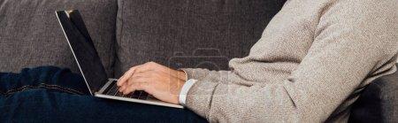 Photo for Cropped view of man typing on laptop keyboard on sofa, panoramic shot - Royalty Free Image