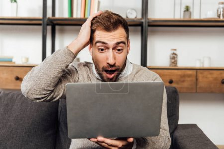 Photo pour Shocked man looking at laptop on sofa in living room - image libre de droit