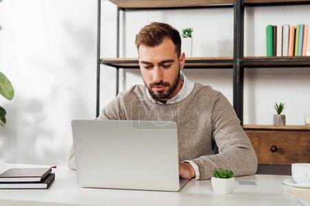 Photo pour Handsome man using laptop while working at table - image libre de droit
