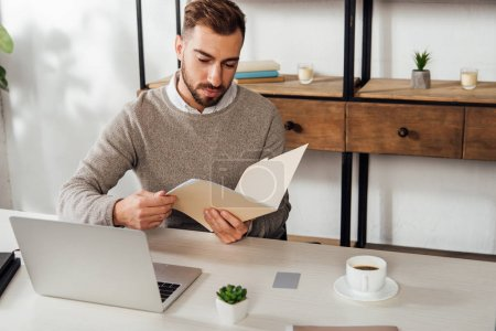 Photo for Man holding paper folder beside laptop and coffee on table - Royalty Free Image