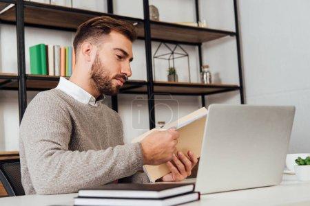 Foto de Man holding paper folder beside laptop and notebooks on table - Imagen libre de derechos