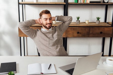 Photo pour Smiling man with hands beside head looking at laptop on table - image libre de droit