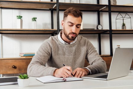 Photo for Man writing on notebook beside laptop on table - Royalty Free Image