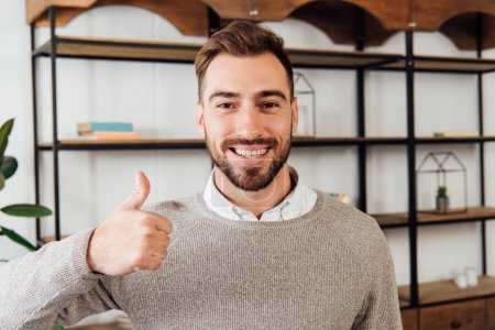 Photo for Handsome man showing thumb up gesture and smiling at camera - Royalty Free Image