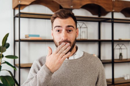 Exited man covering mouth with hand and looking at camera