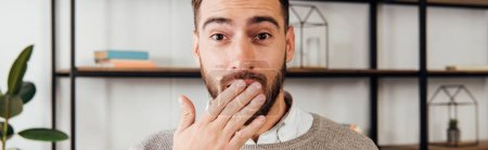 Exited man covering mouth with hand and looking at camera, panoramic shot