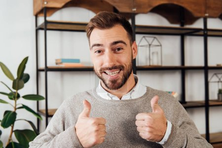 Photo for Handsome man showing thumbs up gesture and smiling at camera - Royalty Free Image