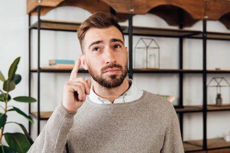 Photo pour Pensive man pointing up with finger at home - image libre de droit