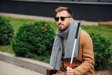 Photo pour Blind man in sunglasses holding walking stick on bench - image libre de droit