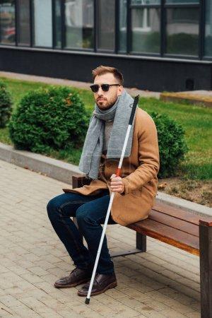Photo pour Aveugle en manteau tenant un bâton de marche assis sur un banc - image libre de droit