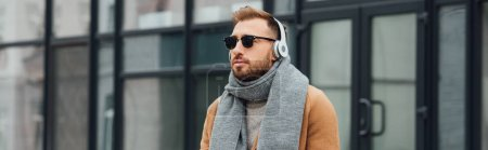 Panoramic shot of handsome man in coat and headphones outdoors