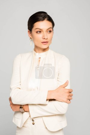 Photo pour Grave élégante femme d'affaires avec les bras croisés en costume blanc, isolé sur gris - image libre de droit