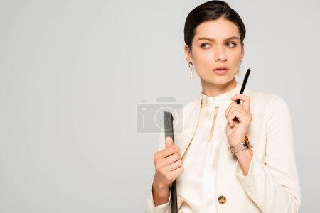 Photo pour Femme d'affaires réfléchie en costume blanc tenant le presse-papiers et le stylo, isolée sur gris - image libre de droit