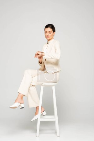 elegant businesswoman in white suit looking at watch while sitting on stool, on grey