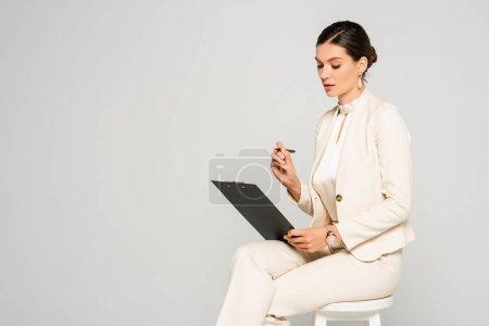 Photo pour Élégante jolie femme d'affaires en costume blanc assise sur tabouret avec stylo et presse-papiers, isolée sur gris - image libre de droit